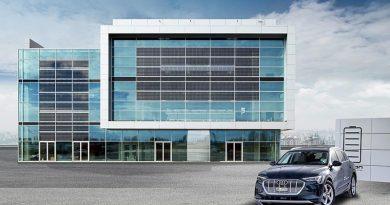 Das Event- und Konferenzgebäude Brand Experience Center der AUDI AG am Flughafen München verfügt über 1.650 Photovoltaik-Elemente (dunkle Glasflächen), deren Strom für die Versorgung des Gebäudes und der Ladestationen für E-Fahrzeuge genutzt wird. Quelle: AUDI AG
